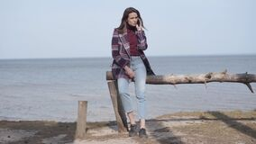 Serious brunette woman talking on the phone on riverbank. Portrait of confident Caucasian lady in casual jeans and plaid