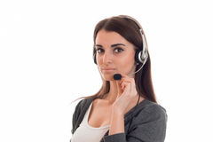 Serious brunette woman working in call center with headphones and microphone looking at the camera isolated on white Stock Photos