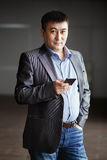 Serious brutal asian business man with phone in his hands, courageous suit portrait. Gray blue tones. Ready to go. Royalty Free Stock Image