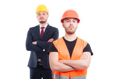 Serious builder and architect behind him Royalty Free Stock Photos