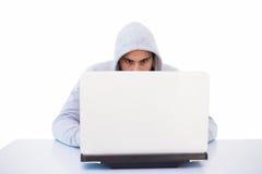 Serious burglar hacking into laptop Royalty Free Stock Photos