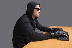 Serious burglar hacking into laptop Royalty Free Stock Photography