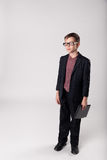 Serious business child boss with laptop. Portrait of serious business child boss in a suit and eyeglasses holding laptop in his hands Royalty Free Stock Photography