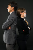 Serious business couple standing back to back. Isolated on gray Royalty Free Stock Image