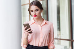 Serious business girl is sending message by phone Stock Images