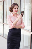 Serious business girl is sending message by phone Royalty Free Stock Images