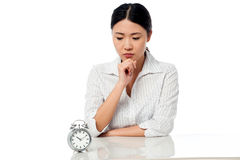 Serious business lady staring at alarm clock Royalty Free Stock Photography