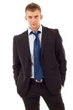 Serious business man. Standing with hands in pockets. Isolated on white background royalty free stock image