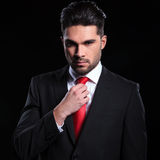 Serious business man adjusts his tie Stock Images