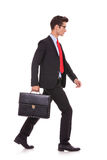 Serious business man with briefcase and walking Royalty Free Stock Photography