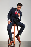 Serious business man in elegant double breasted suit sitting Royalty Free Stock Photo