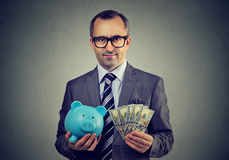 Serious business man in glasses with piggy bank and dollar cash banknotes stock photography