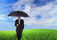 Serious business man holding black umbrella. Serious business man standing oh the green field and holding black umbrella, concept for business Stock Photo