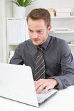 Serious business man with laptop. Serious young business man in the office with laptop Royalty Free Stock Photography