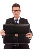 Serious business man offering a briefcase Stock Image