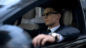 Serious business man sitting in car, waiting in traffic jam, transportation stock photo