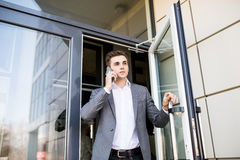 Serious business man in suit talking on phone in office and holding the door Royalty Free Stock Images