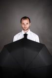 Serious business man with umbrella Royalty Free Stock Images