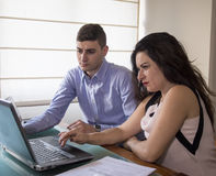 Serious business man and woman looking at laptop screen at home office Royalty Free Stock Photography