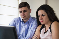 Serious business man and woman looking at laptop screen at home office Royalty Free Stock Images
