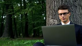 Serious business man working on laptop, sitting under tree in central park royalty free stock photo