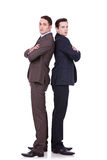 Serious business men standing back to back. Full body picture of two serious business men standing back to back over white background Royalty Free Stock Image