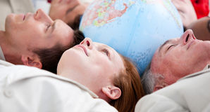Serious business people lying around a globe Royalty Free Stock Photography