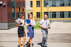 Serious business people walking and looking to camera. Three colleagues walk on the innovation centre Stock Image