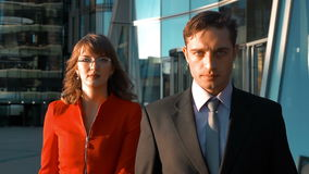 Serious business people walking outdoor. Two serious business people, male in black suit, tie and white shirt, female in sexy red suit and spectacles walking and stock video footage