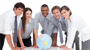 Serious business team around a terrestrial globe. Self-assured business team around a terrestrial globe against a white background stock photo