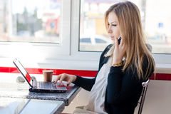Serious business woman beautiful young blond woman talking on the mobile cell phone working on a laptop pc computer in restaurant Royalty Free Stock Images