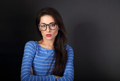 Serious business woman in blue clothing and eye glasses looking. With folded arms on gark grey background with empty copy space Royalty Free Stock Photo