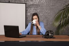 Serious business woman is drinking coffee, copy space behind her. Back stock photo