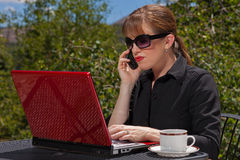 Serious business woman on laptop. Serious business woman with sunglasses on sitting at an outdoor table with her laptop and cell phone Stock Photo