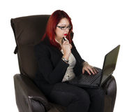 Serious business woman with laptop. Serious business woman sitting on the couch with her laptop. White background Stock Photography