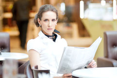 Serious business woman reading newspaper. Serious business woman in cafe reading newspaper while lunch time Stock Image