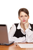 Serious business woman sits on desk in office Stock Photo