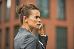 Serious business woman talking cell phone. In front of office building Royalty Free Stock Photography