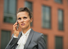 Serious business woman talking cell phone. In front of office building Stock Photography