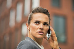 Serious business woman talking cell phone. Portrait of serious business woman talking cell phone in front of office building Royalty Free Stock Photos