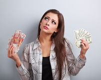 Serious business woman thinking that currency to choose, dollars Royalty Free Stock Image