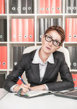 Serious business woman thinking. And writing in the notebook Royalty Free Stock Photo