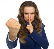 Serious business woman threatening with fist. Isolated on white Stock Photo
