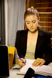 Serious business woman at work writing on agenda in office. Gorgeous woman at work concentrated Royalty Free Stock Photos