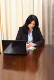 Serious business woman writing in office Stock Image