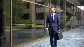Serious business worker going to work, holding briefcase, business center stock images