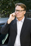 Serious businessman. A pensive looking  businessman wearing spectacles listens to bad news on his cellphone Stock Photos