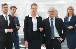 Serious businessman and business woman on the background of the office staff. Stock Images