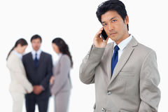 Serious businessman on cellphone with team behind him Stock Images