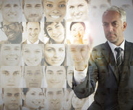 Serious businessman choosing future employees. On digital interfaces Royalty Free Stock Photo